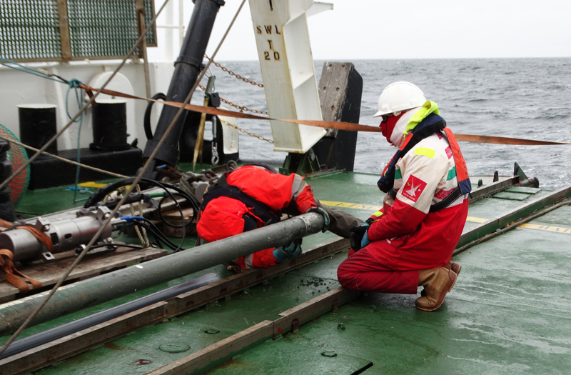 Scientists on the OGS Explora open a gravity core that contains mud recovered from below the sea floor of the Ross Sea.