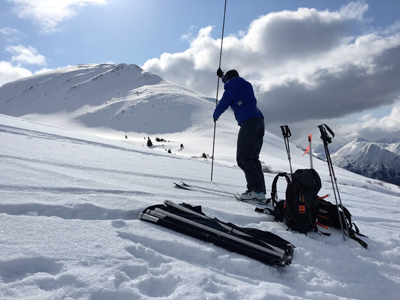 A scientist measures snow depth with an avalanche probe