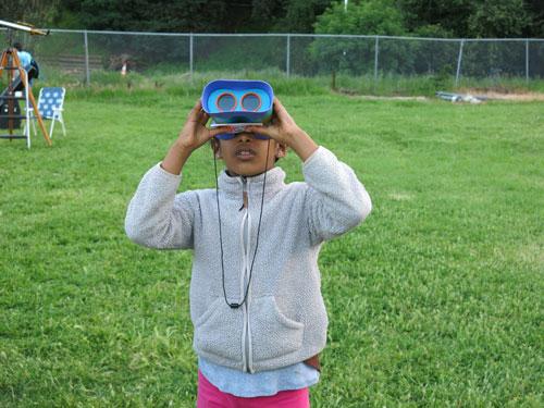 A Girl Scout looking through solar binoculars