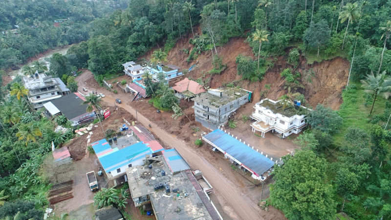 Debris from a landslide stacked against homes in Idukki, India.