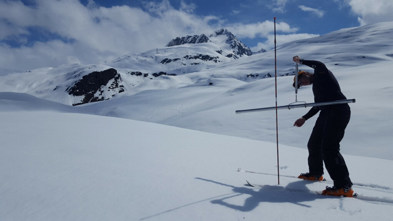 A researcher measures snow-water equivalent in Alaska