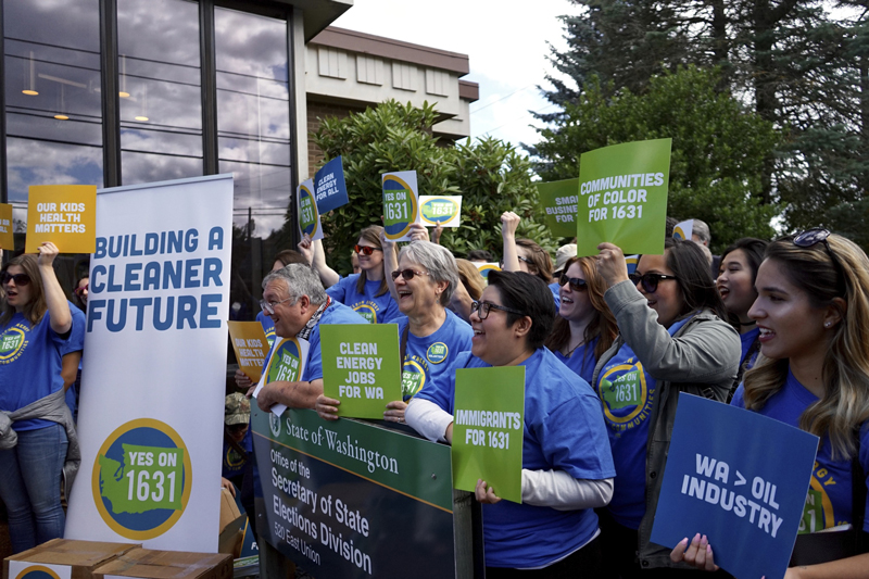 Individuals rally in support of Initiative 1631 in Washington State.