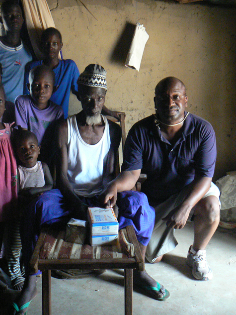 Gregory Jenkins (kneeling at right) visits a village chief in the West African nation of Senegal.