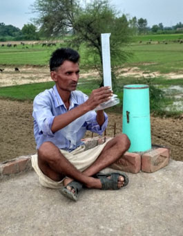 A volunteer checks a manual rain gauge.