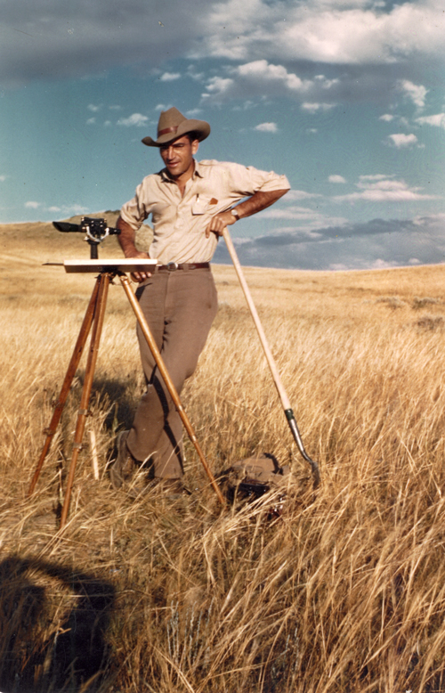 Luna Leopold, river geomorphology innovator, uses surveying gear in dry grass field in Montana.
