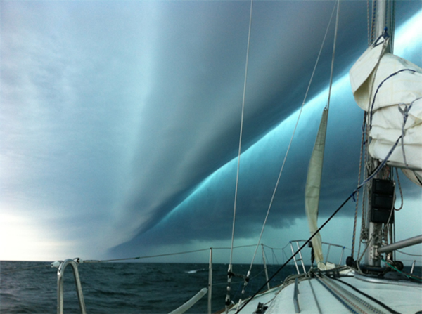 A storm cloud forms over the ocean, as seen from the prow of a boat