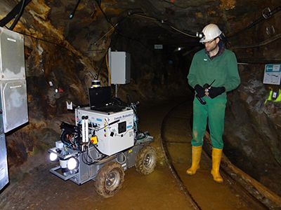 A man operates a rover in a mine shaft.