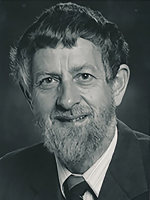 Alt/title text: Black-and-white portrait of Ian McDougall, a bearded white man in a suit
