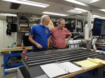 Two men examine sediment cores in a lab setting