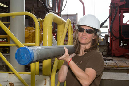 Woman in a hard hat carries a long sediment core
