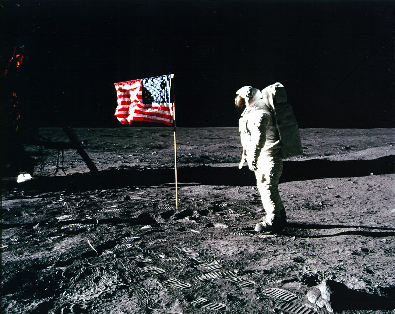 An astronaut faces the American flag on the Moon.