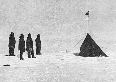 Black-and-white photo of white explorers at the South Pole gazing at a tent with a Norwegian flag