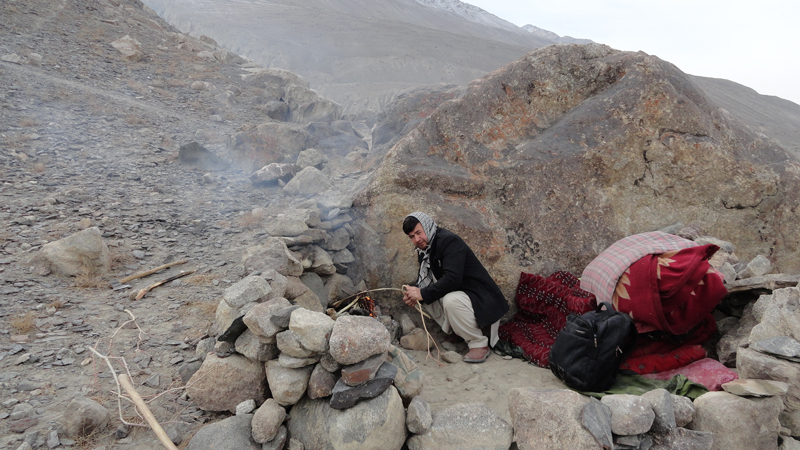 Man starts a fire in a rocky landscape.