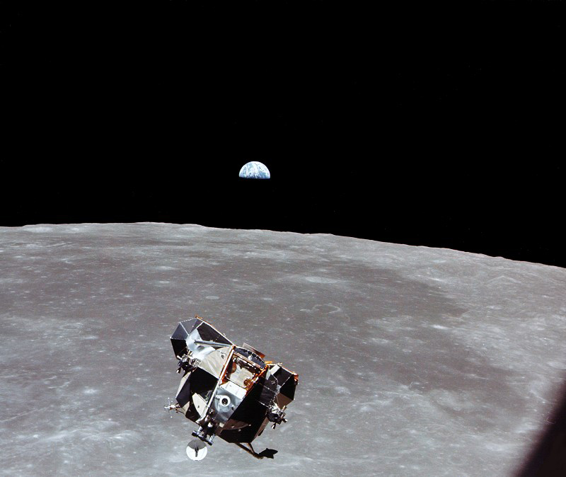 Earth rises over a lunar horizon with a spacecraft in the foreground.