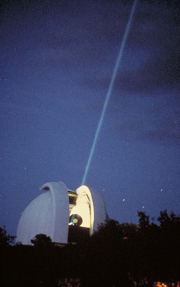A laser beam shines out of an observatory.