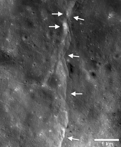 Black-and-white satellite image of the lunar landscape with arrows pointing to a ridge