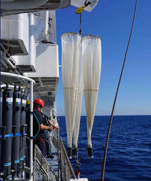 Crew members prepare to deploy plankton nets during a research cruise.