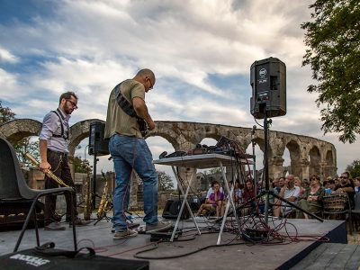 Two musicians play on stage in front of an outdoor audience at an ancient Roman theater.
