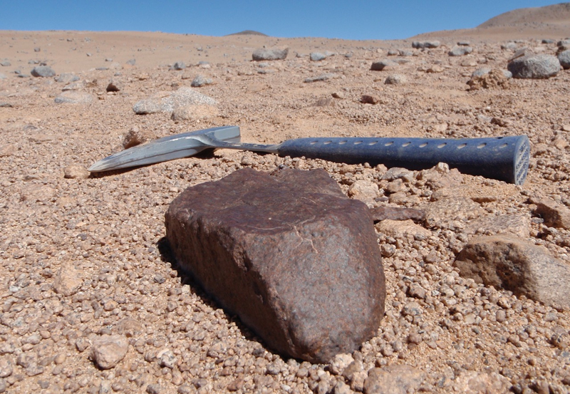 A large brown meteorite the size of a football sits among smaller lighter rocks and a rock hammer for scale.