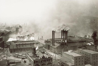 Black-and-white aerial photo of smokestacks polluting a city