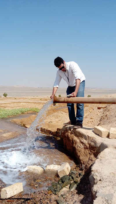 Man collects water from a pipe in the desert.