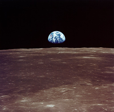 Earth rises over the horizon of the Moon.