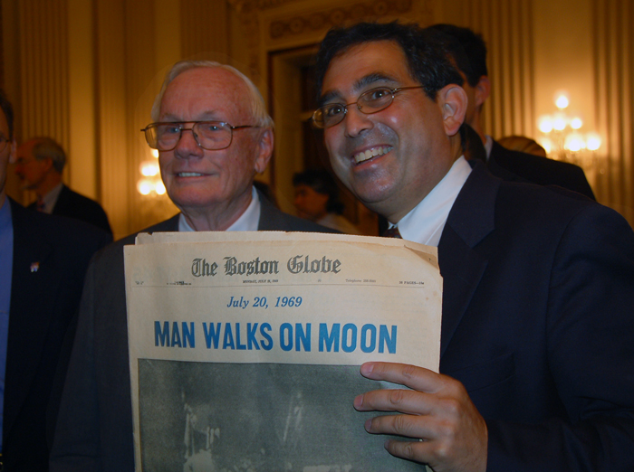 """Neil Armstrong poses with Randy Showstack and a Boston Globe front page reading """"Man Walks on Moon."""""""