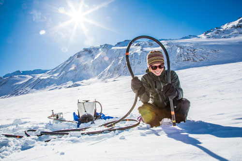 Photo of a smiling woman conducting an experiment on a glacier