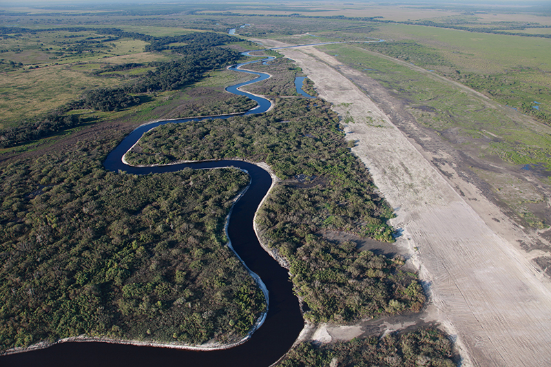 Aerial photo of a restored stretch of Florida's Kissimmee River beside the backfilled C-38 canal