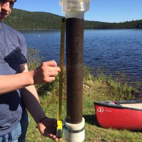 A researcher holds a sediment core collected from the bottom of Lake Sinclair.