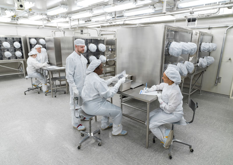 Photo of scientists in protective gear in a lab
