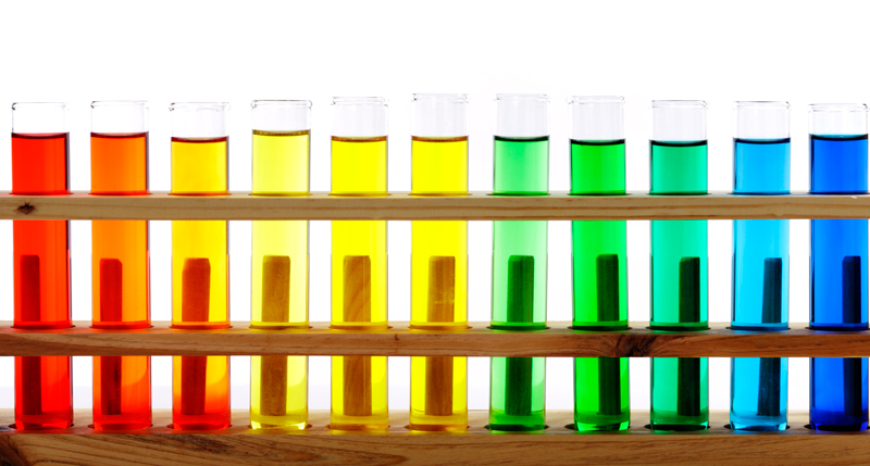 Test tubes in a row filled with colored liquid form a rainbow