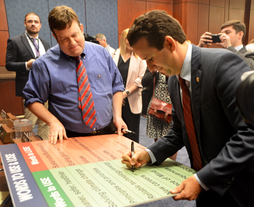 "Sen. Brian Schatz (D-Hawaii) signs pollster Frank Luntz's ""Words To Use & Lose"" poster after the hearing."