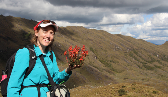 A photograph of biogeographer Suzette Flantua holding a scarlet-colored flower that may be part of a new species of plant.