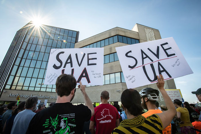 "Photo of a protest with ""Save UA"" signs outside the Anchorage Legislative Building"