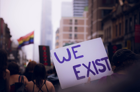 "A person in a crowd holds up a sign saying ""We Exist"" with a rainbow flag flying in background"