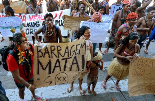 Indigenous Brazilian people protest with signs