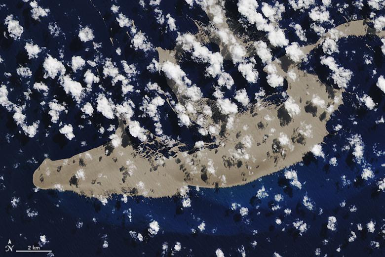 Satellite image of a huge raft of floating grey rocks in the ocean