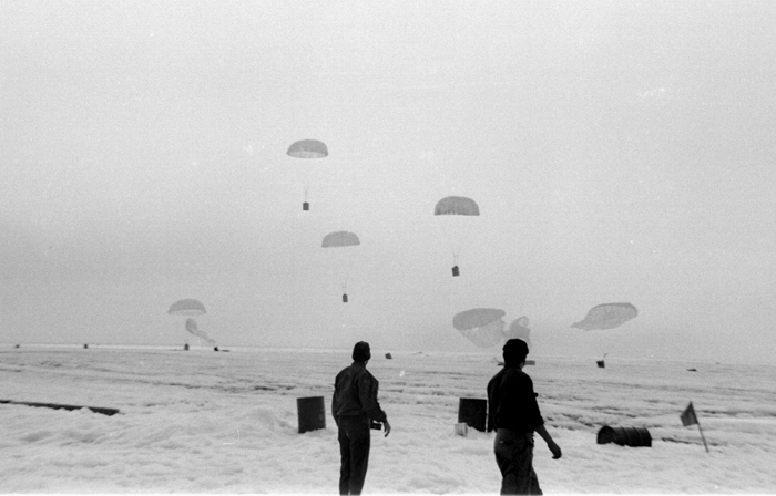 Black-and-white photo of parachuted boxes landing on ice island