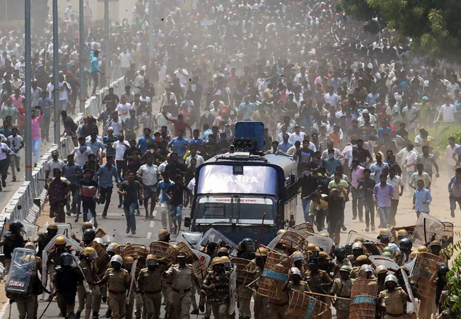A large group of protesters approach a police barricade in India