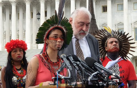 Indigenous Amazonians in traditional garb speak at a podium with a translator in a suit.
