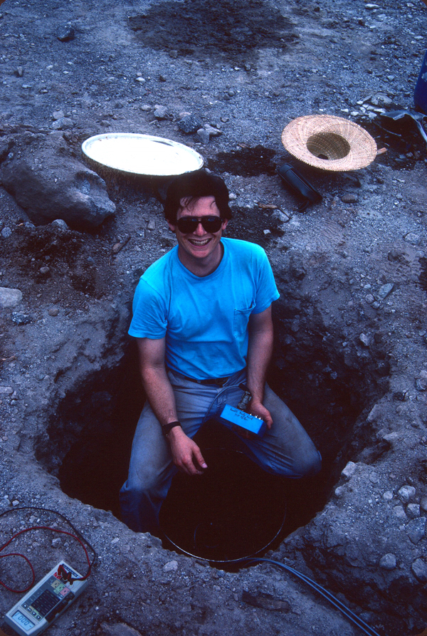 A smiling volcanologist installs a tiltmeter in a hole in the ground.