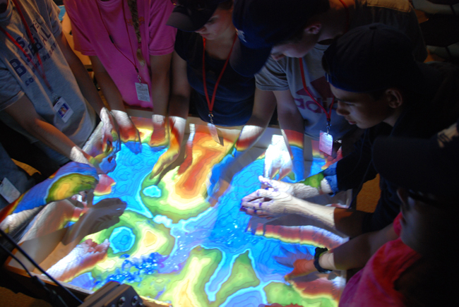 Student hands create geological features in an augmented reality sandbox.