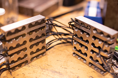 Acoustic sensors mounted in steel plates that detect sounds emitted during testing at Penn State's earthquake machine.