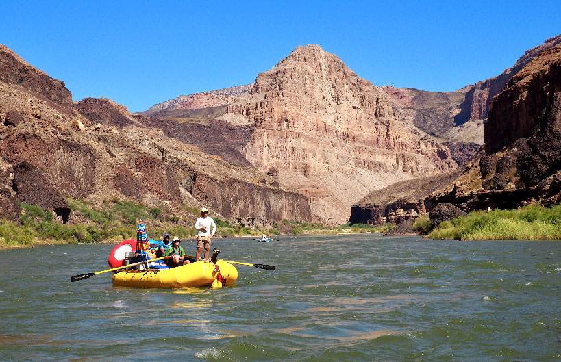 Three men raft by extensive ancient lava flows that appear on both sides of the river.