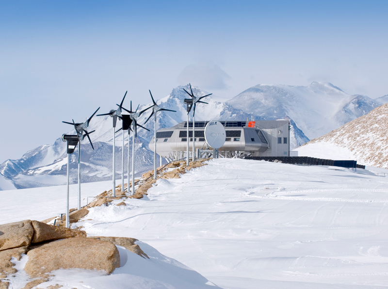 Wind turbines line an icy, snowy path to a Space Age-looking research station in Antarctica.