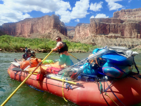 A man in a Hawaiian shirt and a mohawk rows a big red raft with one passenger down the Colorado River.