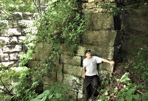 Photo of a man standing near a wall of large concrete blocks overgrown with vegetation
