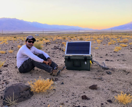 Photo of a man sitting in a rocky desert with a small solar-powered seismic station