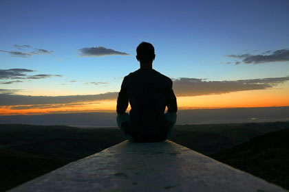 Silhouette of a person meditating at sunrise